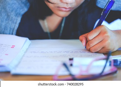 Close up secondary school girl 's left hand writing on paper, do homework on wooden table in room, student  girl holding blue pen doing homework, or doing examination with stressed ,education concept