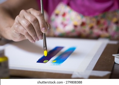 Close up section of female painter artist - hand leading brush. Woman painting a picture