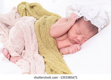 Close up selective focus 0-10 days sleeping young cute newborn baby infant lie down on white wool blanket or soft towel, sleeping newborn baby 0-10 days on white background with copy space
