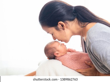 Close up selective focus beautiful mother kiss her little girl baby, mother taking care newborn baby at home, lifstyle of modern mother taking care little baby 0-10 days concept