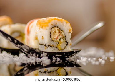 Close up of selective focus of delicious sushi rolls over a metallic spoon with small grains of salt served on black table