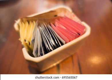 close up the selective focus of different colored and different types of sugar packets in the ceramic container