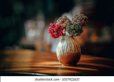 Close up and selective focus dry flowers in vase on wooden table in dining room or restaurant,still life concept.