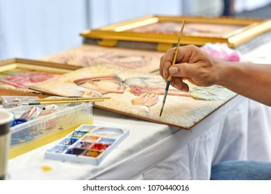 Close up and selective focus hand of Thai artist holding the paintbrush is drawing the King Majesty Rama 9 of Thailand image on a quadrilateral frame.April 17,2018 : Chiang Mai,Thailand.