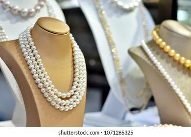 Close up and selective focus many pearl neckless show in a shop with blurred space and bokeh.