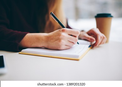 Close up of selective focus on woman's hands writing information to textbook for education using quality black pen, cropped image of female sitting at cafeteria table with notepad in coffee shop