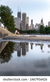 A close up selective focus photograph of a puddle on concrete sidewalk or walkway with curb with the Chicago skyline high rise buildings, a person and tree blurred in the bokeh background beyond.
