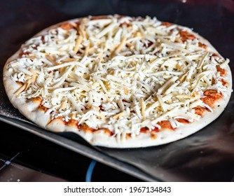 Close and selective focus of a readymade frozen stone baked thin four cheese pizza on a baking mat ready to be cooked in the oven for Saturday night dinner
