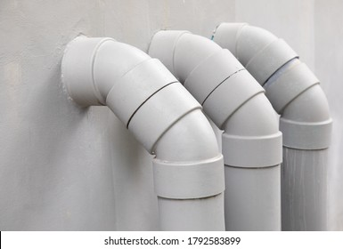 Close Up and selective focus shot of curved and bent PVC plastic tube pipes for water circulation system draining waste from urban house or apartment on white cement wall in vertical direction.