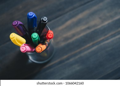 Close up selective focus of stack of Colored Pens Markers  In A Cup on the Dark Wooden Background with copy space for your text. Back to school and offices stationary concept.