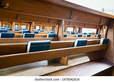 close up selective focus view of many wooden church pews with blue bibles