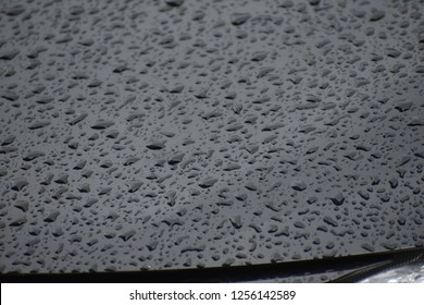 Close up and selective focus water drops or water stains with reflection on the front of the black car for Illustrations cleanin,coloring car paint or rainy season.