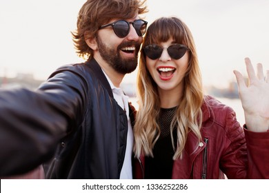 Close up self portrait of cute playful couple having fun and spending romantic moments together . Wearing stylish leather jacket and sunglasses.  Happy emotions.