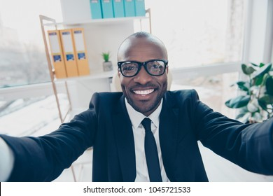 Close up self portrait of stylish, cheerful, attractive man shooting selfie in two hands, smiling at camera, standing in work place, station, having fun, timeout