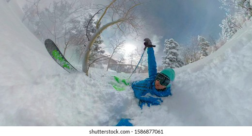 CLOSE UP SELFIE: Active male tourist crashes while tree skiing in picturesque Deer Valley. Funny shot of a cross-country skier slamming into the soft cold smoke while skiing in the American mountains.