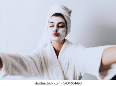 Close up selfie of beautiful happy woman after shower with a towel on her head sending air kiss with cream on face.Woman with clay mask taking selfie with mobile phone at home enjoying relaxation and