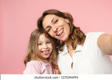 Close up selfie shot woman in light clothes have fun with cute child baby girl. Mother, little kid daughter isolated on pastel pink wall background, studio portrait. Mother's Day, love family concept