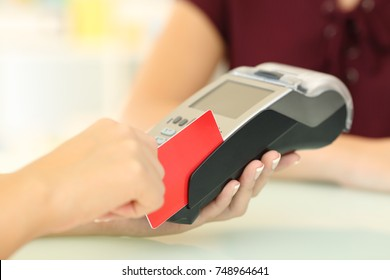Close up of a seller hands using a dataphone to charge with a credit card in a store desk