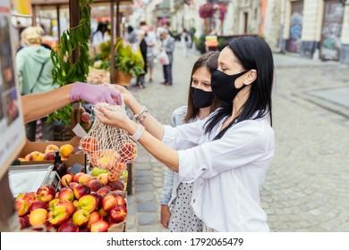 Nahaufnahme von Händen des Verkäufers in Schutzhandschuhen, die organische Pfirsich in einem Maschenbeutel verpacken. Zwei weibliche Käufer in Schutzmasken wählen Pfirsiche auf dem Bauernmarkt. Neue soziale Regeln nach der Pandemie.