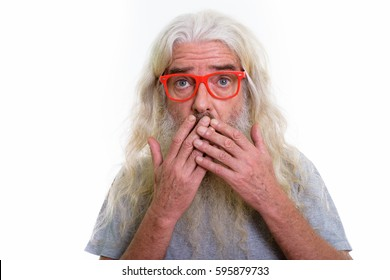 Close up of senior bearded man thinking while looking shocked and covering mouth with both hands
