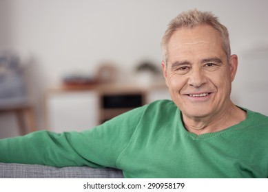 Close up Senior Blond Man in Green Shirt, Sitting on Sofa at Home and Smiling at the Camera