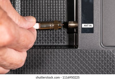 Close up of senior caucasian man hand removing the aerial connection to his TV to illustrate cutting the cable TV cord