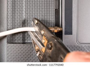 Close up of senior caucasian man hand cutting the aerial connection to his TV to illustrate cutting the cable TV cord