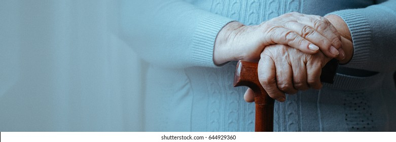 Close up of senior disabled woman's hands holding walking stick