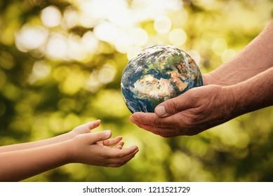 Nahaufnahme von Senior Händen, die einem Kind auf entfokussiertem grünem Hintergrund mit Kopienraum kleine Erde geben