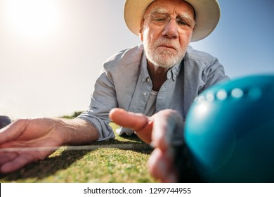 Close up of a senior man lying on ground and measuring the distance between boules using a measuring device. Senior man checking the distance between a boules and the jack to know the result.