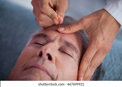 Close up of senior man receiving head massage from physiotherapist in clinic