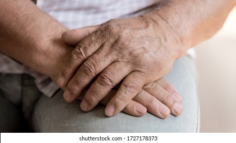 Close up of senior man sit hold hands feeling lonely or abandoned in retirement house, old male patient thinking pondering of life problems, miss good old days, elderly solitude, loneliness concept