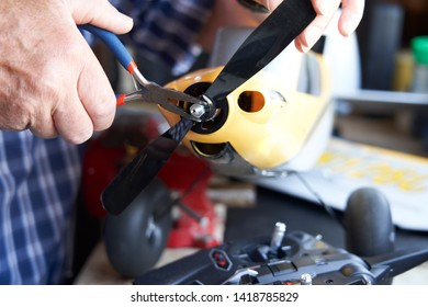 Close Up Of Senior Man Working On Model Radio Controlled Aeroplane In Shed At Home