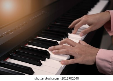 Close up senior woman hand with frickle playing electronic paino at home, relaxing time with music, practice music, learning music at home concept. Light at the coner.