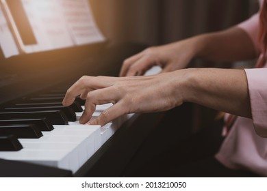 Close up senior woman hand playing electronic paino at home, relaxing time with music, practice music, learning music at home with light at the coner.