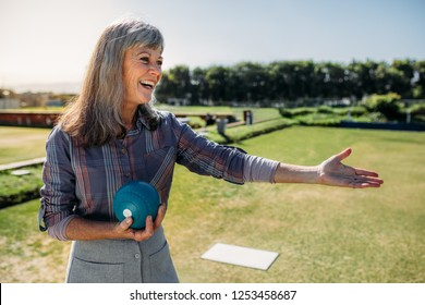 Close up of a senior woman playing boules in a park. Smiling woman with a boules in hand standing in a lawn ready to throw.