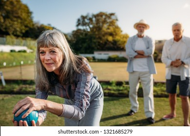 Close up of a senior woman playing boules with her male friends standing in the background. Old woman bending forward to throw a boules in a park.