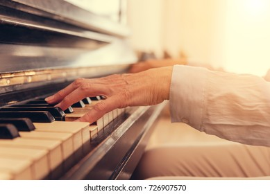Close up of senior woman playing the piano