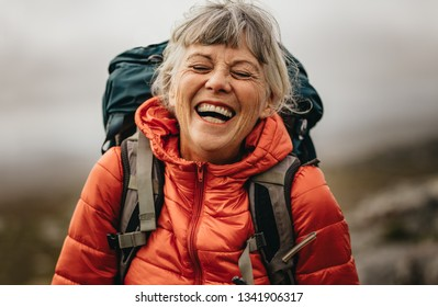 Close up of a senior woman wearing jacket and backpack laughing with eyes closed. Portrait of a woman hiker laughing during her trekking.