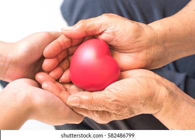 Close up of senior woman and young female hands holding red heart.National Family Caregivers Month, National Hospice Month and National Home Care Month. Age, family, love and health care concept