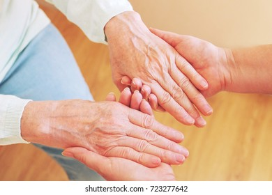 Close up of senior woman and young woman holding hands. Care and support concept