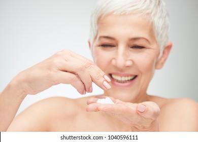 Close up of senior woman`s hands applying cream.