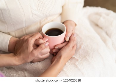 Close Up Of Senior Woman's Hands Holding A Pink Cup Of Aromatic Tea. Hugge Or Lagom Concept