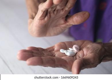 close up of senior women hand taking pills