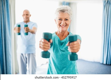 Close up of seniors using weights in a retirement home