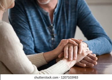 Close up of sensual aged husband and wife holding hands enjoying romantic moment at home, caring senior couple caress and comfort each other, having tender sincere talk. Elderly love concept