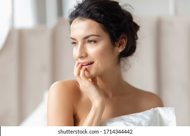 Close up sensual beautiful woman face bedroom portrait. Side view on female looking aside and touching chin with hand. Pretty seductive brunette girl with naked shoulders on blurred space