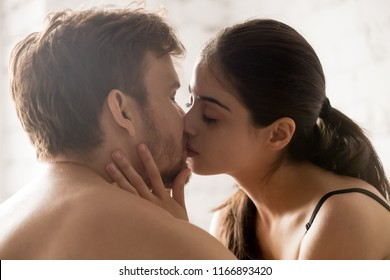 Close up of sensual young couple kissing in bedroom having romantic foreplay before sex, tender lovers caress making peace or reconcile after serious fight, boyfriend and girlfriend enjoy intimacy