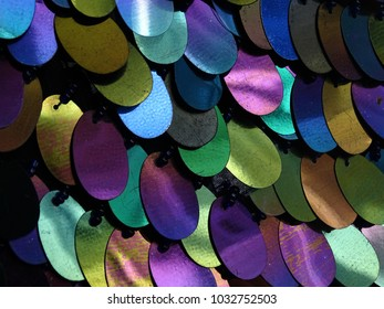 A close up of a sequin background with purple, green, yellow and blue droplet sequins