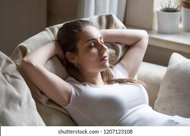 Close up serene tranquil woman smiling lying on couch at home or hotel room girl has break after work or study closing eyes putting hands behind head relax think, feels happy breath fresh air concept